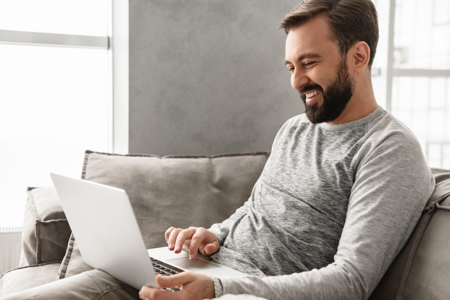 Image of a smiling young man seated on a couch using his laptop computer
