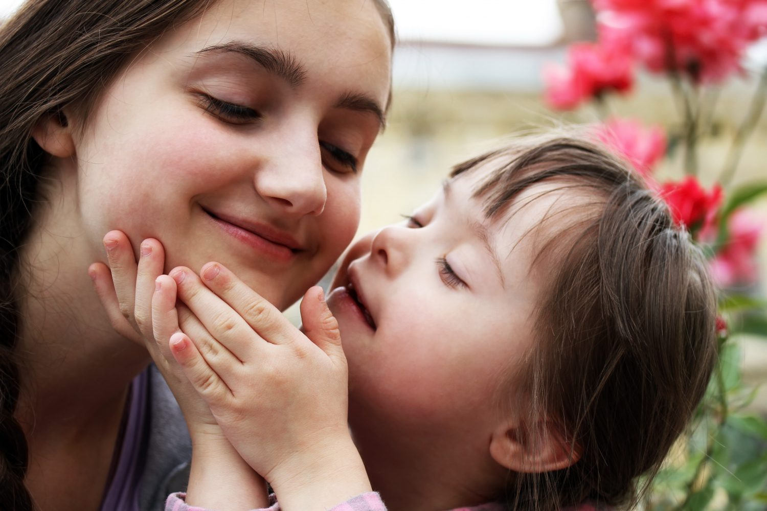 : Image of a smiling young girl with Down syndrome touching the face of another girl